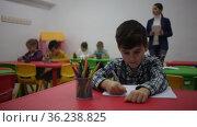Preteen boy studying in classroom on background with classmates and teacher. Стоковое видео, видеограф Яков Филимонов / Фотобанк Лори