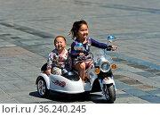 6 bis 8jähriges Mädchen fährt mit ihrem Bruder auf einem elektrisch... Стоковое фото, фотограф Zoonar.com/GFC Collection / age Fotostock / Фотобанк Лори
