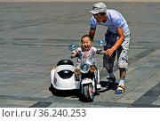 Kleinkind fährt mit Unterstützung seines Vaters ein elektrisch betriebenes... Стоковое фото, фотограф Zoonar.com/GFC Collection / age Fotostock / Фотобанк Лори