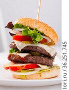 Double tasty hamburger with beef cutlet, fresh vegetables and cheese. Стоковое фото, фотограф Яков Филимонов / Фотобанк Лори