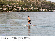 Young, sporty guy rides a surfboard with a paddle in his hand on a sunny summer day (2020 год). Редакционное фото, фотограф Татьяна Ляпи / Фотобанк Лори