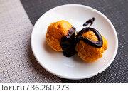 Appetizing profiteroles with filling of pastry cream served with dark chocolate. Стоковое фото, фотограф Яков Филимонов / Фотобанк Лори