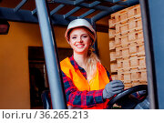 Beautiful smiling woman with makeup, forklift truck driver, wearing... Стоковое фото, фотограф Zoonar.com/Oksana Shufrych / easy Fotostock / Фотобанк Лори
