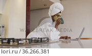 African american attractive woman with applied face mask drinking coffee and using laptop in kitchen. Стоковое видео, агентство Wavebreak Media / Фотобанк Лори