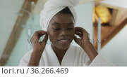 Smiling african american attractive woman putting towel on head and looking at mirror in bathroom. Стоковое видео, агентство Wavebreak Media / Фотобанк Лори