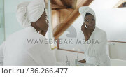 African american attractive woman removing make up in bathroom. Стоковое видео, агентство Wavebreak Media / Фотобанк Лори