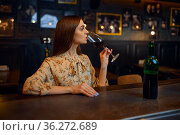Young woman drinks red wine at the counter in bar. Стоковое фото, фотограф Tryapitsyn Sergiy / Фотобанк Лори