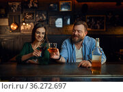 Happy couple drinks alcohol at the counter in bar. Стоковое фото, фотограф Tryapitsyn Sergiy / Фотобанк Лори