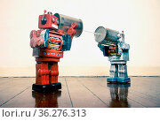 Two retro Robots toys talking on tin can phones on an old wooden floor. Стоковое фото, фотограф Zoonar.com/charles taylor / easy Fotostock / Фотобанк Лори