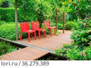 Three red chairs in a green garden. Стоковое фото, фотограф Zoonar.com/Hilda Weges / easy Fotostock / Фотобанк Лори
