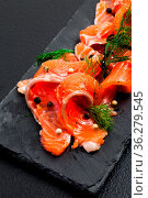 Smoked Salmon with peppercorns and dill close up on the black slate. Стоковое фото, фотограф Zoonar.com/Oksana Shufrych / easy Fotostock / Фотобанк Лори