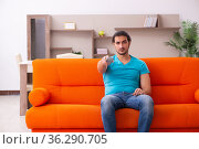 Young male student watching tv indoors. Стоковое фото, фотограф Elnur / Фотобанк Лори