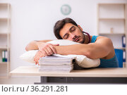 Young male employee coming to work straight from bed. Стоковое фото, фотограф Elnur / Фотобанк Лори