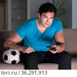 Young man watching football late at night. Стоковое фото, фотограф Elnur / Фотобанк Лори