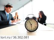 Alarm clock on office table with business discussion people group... Стоковое фото, фотограф Zoonar.com/Tatiana Badaeva / easy Fotostock / Фотобанк Лори