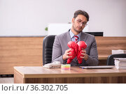 Young male employee wearing boxing gloves at workplace. Стоковое фото, фотограф Elnur / Фотобанк Лори