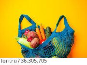 Organic farm marke. Vegetables in mesh cotton bag on yellow background. Стоковое фото, фотограф Zoonar.com/Oksana Shufrych / easy Fotostock / Фотобанк Лори