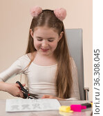 Веселая девочка школьного возраста вырезает из бумаги пасхальных зайцев. Стоковое фото, фотограф Наталья Гармашева / Фотобанк Лори