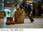 Rifle and hunting boots at the stump in gun store. Стоковое фото, фотограф Tryapitsyn Sergiy / Фотобанк Лори