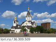 Cyclists near white church of Holy Apostles Constantine and Elena. Moscow. Редакционное фото, фотограф Валерия Попова / Фотобанк Лори
