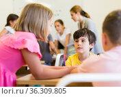 Interested tween boy discussing teacher assignment with classmates. Стоковое фото, фотограф Яков Филимонов / Фотобанк Лори