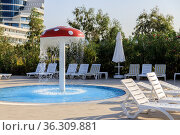 Sun loungers are located near the pool with a children's fountain-waterfall in the form of a mushroom muhamor. Стоковое фото, фотограф Tetiana Chugunova / Фотобанк Лори