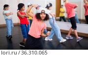 Smiling preteen mulatto girl dancing hip hop during group class. Стоковое фото, фотограф Яков Филимонов / Фотобанк Лори