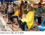 BATU CAVES, MALAYSIA - JANUARY 29, 2011: Barber shaving mens heads... Стоковое фото, фотограф Zoonar.com/Alexander Ludwig / age Fotostock / Фотобанк Лори