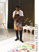 African american male painter at work looking at artwork in art studio. Стоковое фото, агентство Wavebreak Media / Фотобанк Лори