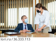 Two business partners in protective masks discuss a new business project, signing documents. Стоковое фото, фотограф Яков Филимонов / Фотобанк Лори