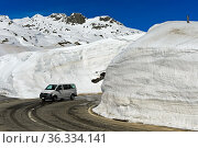 PKW fährt auf der Passtrasse zwischen hohen Schneemauern über den... Стоковое фото, фотограф Zoonar.com/Georg / age Fotostock / Фотобанк Лори