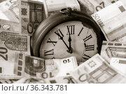 Euro Geldscheine und eine Uhr, die Zeiger stehen fuenf Minuten vor... Стоковое фото, фотограф Zoonar.com/Uwe Bauch / easy Fotostock / Фотобанк Лори