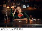 Depressed woman drinks alcohol at counter in bar. Стоковое фото, фотограф Tryapitsyn Sergiy / Фотобанк Лори