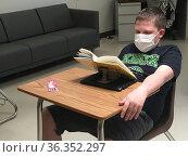 Middle School Boy Reading a Book, Wearing Mask, Wellsville, New York... Редакционное фото, фотограф Barrie Fanton / age Fotostock / Фотобанк Лори