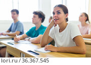 Smiling girl high school student listening to teacher during lesson. Стоковое фото, фотограф Яков Филимонов / Фотобанк Лори