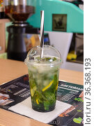 A glass plastic cup with mojito on a table. Стоковое фото, фотограф Сергей Бочаров / Фотобанк Лори