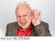 Schwerhöriger Senior hält Hand an Ohr auf hellem Hintergrund. Стоковое фото, фотограф Zoonar.com/Birgit Reitz-Hofmann / age Fotostock / Фотобанк Лори