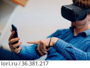 Young man in virtual reality goggles, vr glasses headset with joystick... Стоковое фото, фотограф Zoonar.com/Max / easy Fotostock / Фотобанк Лори