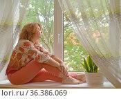 Женщина средних лет сидит на подоконнике и с интересом смотрит в окно. Стоковое фото, фотограф Ирина Борсученко / Фотобанк Лори