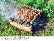 Grilled appetizing kebab cooking on metal skewers. Shashlik during... Стоковое фото, фотограф Zoonar.com/Alexander Blinov / easy Fotostock / Фотобанк Лори