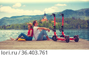 Young couple using electric scooter as modern ecological mean of transport while exploring green country Slovenia at vacations. Green eco energy concept with zero emission. Warm sunshine filter. Стоковое фото, фотограф Matej Kastelic / Фотобанк Лори