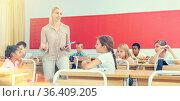 Woman teacher talking with pupils at classroom. Стоковое фото, фотограф Яков Филимонов / Фотобанк Лори