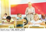 Diligent towheaded preteen girl looking at camera during lesson. Стоковое фото, фотограф Яков Филимонов / Фотобанк Лори
