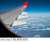 Wing of flying plane from passenger cabin window in blue sky. Стоковое фото, фотограф Яков Филимонов / Фотобанк Лори