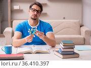 Young male student physicist studying molecular model. Стоковое фото, фотограф Elnur / Фотобанк Лори