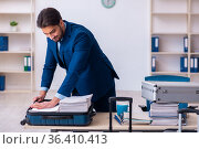 Young male employee preparing for business trip at workplace. Стоковое фото, фотограф Elnur / Фотобанк Лори