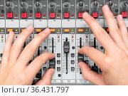 Close-up of a mixing console, hand equalizing audio channels. Professional... Стоковое фото, фотограф Zoonar.com/DAVID HERRAEZ CALZADA / easy Fotostock / Фотобанк Лори