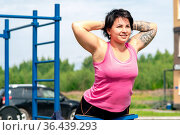 Young woman shakes her back muscles using an outdoor exercise machine hyper extension bench. Стоковое фото, фотограф Евгений Харитонов / Фотобанк Лори