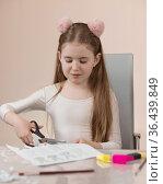 Девочка школьного возраста сидит за столом и вырезает из бумаги поделки. Длинные волосы и ободок с помпонами. Стоковое фото, фотограф Наталья Гармашева / Фотобанк Лори