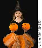 Красивая девочка в костюме ведьмы протягивает оранжевые тыквы-конфетницы. Черный фон. Стоковое фото, фотограф Наталья Гармашева / Фотобанк Лори